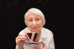 Femme aînée appréciant la cuvette de thé Images stock