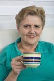 Femme aînée appréciant la cuvette de thé Photos libres de droits