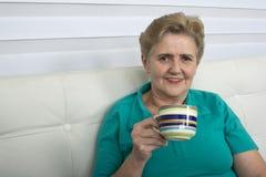 Femme aînée appréciant la cuvette de thé Photos stock