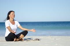 Femme aînée attirante méditant à la plage Photographie stock
