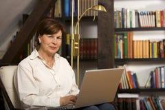 Femme aînée attirante s'asseyant avec l'ordinateur portatif Photo stock