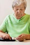 Femme aînée avec des bandes d'essai d'essai de sucre de sang Image libre de droits