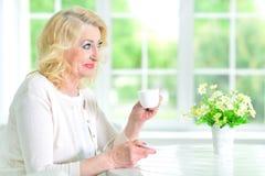 Femme aînée avec la cuvette de thé Images libres de droits