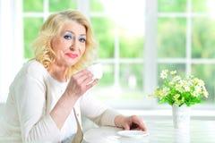 Femme aînée avec la cuvette de thé Image stock