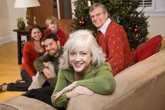 Femme aînée avec la famille par l'arbre de Noël Images stock