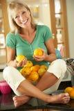 Femme aînée avec le bol d'oranges Photographie stock