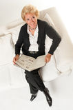 Femme aînée avec le livre sur un sofa Photo libre de droits