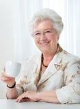 Femme aînée avec une cuvette de café Photos stock