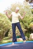 Femme aînée branchant sur le tremplin dans le jardin Photo libre de droits