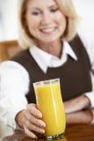 Femme aînée buvant une glace de jus d'orange Photo libre de droits