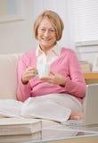 Femme aînée détendant avec du thé sur le sofa à la maison Image libre de droits