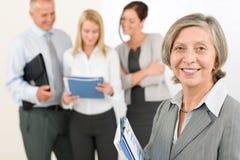 Femme aînée d'équipe d'affaires avec les collègues heureux Photos stock