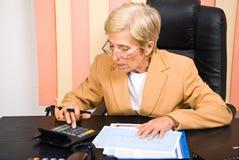 Femme aînée d'affaires à l'aide de la calculatrice dans le bureau Photos libres de droits
