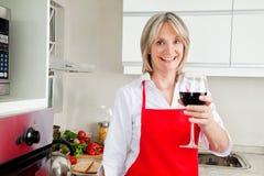 Femme aînée dans la cuisine avec le rouge Photos libres de droits