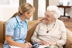 Femme aînée dans la discussion avec le visiteur de santé Images stock