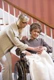 Femme aînée dans le fauteuil roulant à la maison avec l'infirmière Photos libres de droits