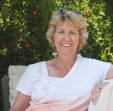 Femme aînée de sourire s'asseyant dans le jardin photos stock