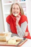 Femme aînée effectuant le sandwich dans la cuisine Photo stock