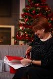 Femme aînée enveloppant des cadeaux de Noël Image stock