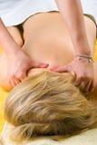 Femme aînée obtenant un massage profond d'épaules Photographie stock