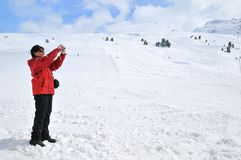 Femme aînée prenant la photo en montagnes de l'hiver Photographie stock libre de droits