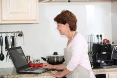 Femme aînée recherchant la recette Photos stock