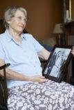 Femme aînée regardant la vieille photo de mariage Photo stock