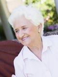 Femme aînée s'asseyant à l'extérieur Photos libres de droits