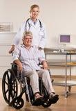 Femme aînée s'asseyant dans le fauteuil roulant avec le docteur Image stock