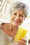 Femme aînée souriant et buvant du jus d'orange Photographie stock