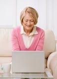 Femme aînée tapant sur l'ordinateur portatif sur le sofa. Photos stock