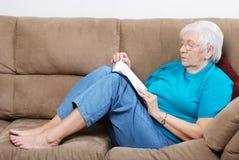 Femme aînée tombant un sommeil tandis que livre de relevé Images stock