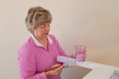 Femme aînée tournant des meubles pour la maison images libres de droits