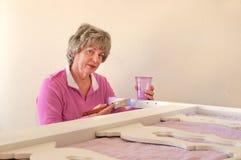 Femme aînée tournant des meubles pour la maison photo libre de droits