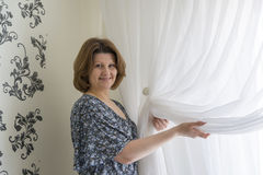 Femme accrochant vers le haut de ses rideaux blancs à la fenêtre Image libre de droits