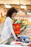 Femme achetant la nourriture de Frozed dans le supermarché Image libre de droits