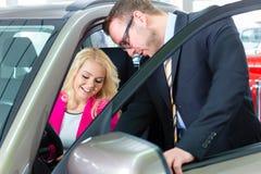 Femme achetant la nouvelle voiture dans l'automobile photographie stock