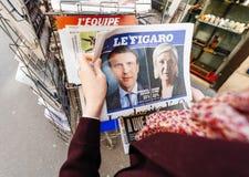 Femme achetant la presse internationale avec Emmanuel Macron et la marine Photographie stock libre de droits