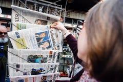 Femme achetant la presse internationale avec Emmanuel Macron et la marine image stock