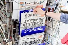 Femme achetant le journal de Le Monde avec le titre choquant au sujet du Br Image libre de droits