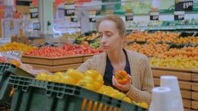 Femme achetant les paprikas oranges frais à l'épicerie clips vidéos