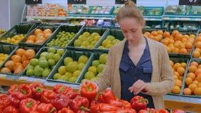 Femme achetant les paprikas rouges frais à l'épicerie clips vidéos