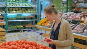 Femme achetant les tomates rouges fraîches à l'épicerie banque de vidéos