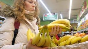 Femme achetant une banane et des légumes en épicerie fine clips vidéos