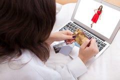 Femme achetant une robe en ligne photos libres de droits