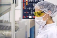 Femme actionnant le panneau de commande - fabrication pharmaceutique image stock