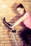 Femme active à l'aide du vélo d'exercice au gymnase photos libres de droits
