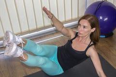 Femme active établissant sur le tapis d'exercice Photo libre de droits