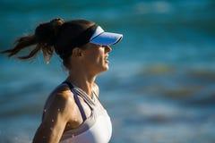 Femme active de sports dans des vêtements de sport fonctionnant contre la mer bleue photo stock