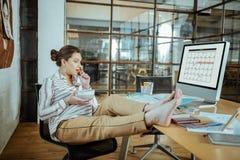 Femme active enceinte appréciant sa pause de midi dans le bureau photographie stock